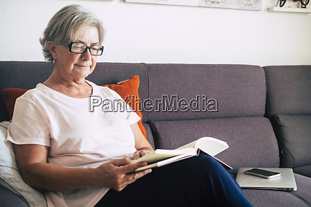 senior woman reading book by laptop