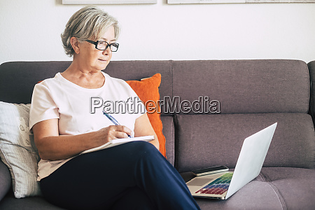 senior woman holding pen using laptop