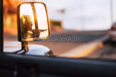 reflection in wing mirror of smiling