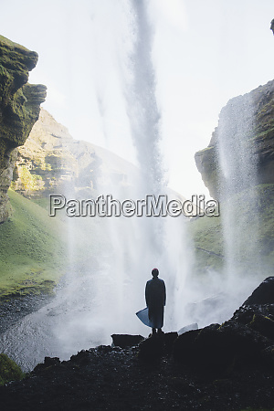 silhouette of man behind kvernufoss waterfall