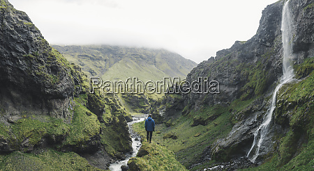 man hiking by waterfall in iceland