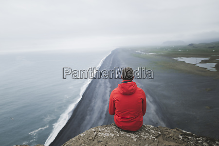 man wearing red coat sitting above