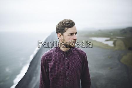 bearded man above beach in vik