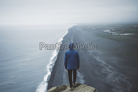 man wearing blue coat above beach