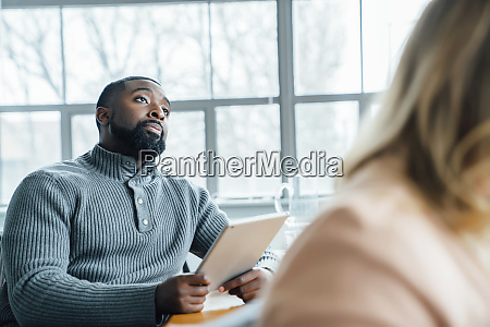 man holding digital tablet during meeting