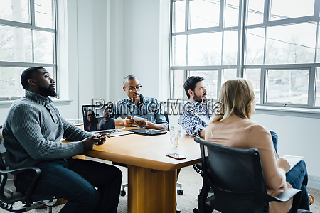 coworkers in boardroom during video call