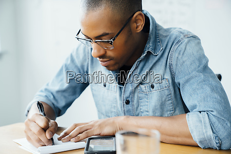 man wearing glasses writing on note