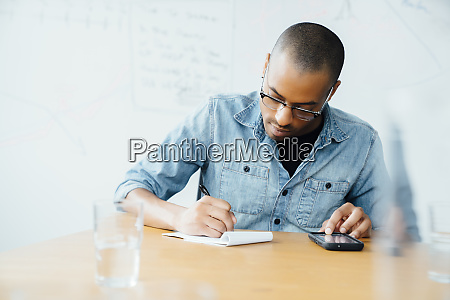 man using smart phone while writing