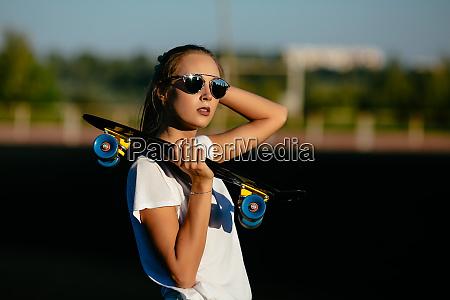a beautiful girl in sundlasses holds