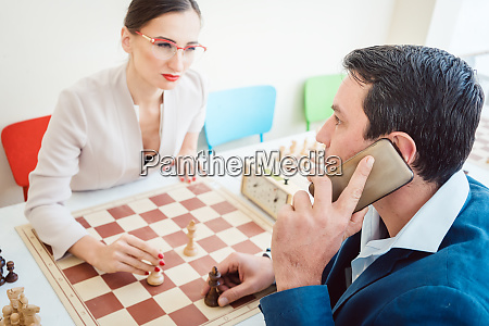 business people playing chess with man