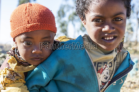 ethiopian girl carrying a little boy