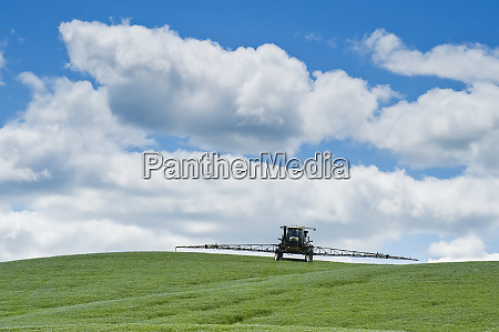 a high clearance sprayer applies a