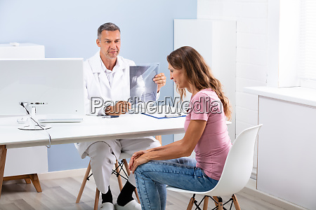 doctor showing knee x ray to