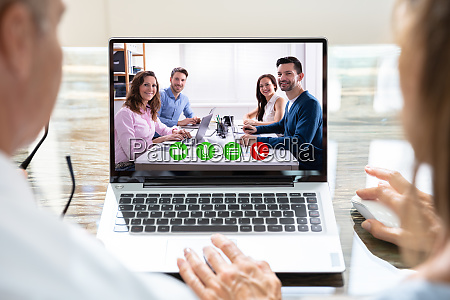 businesspeople video conferencing with colleagues on