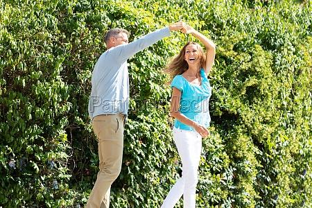 mature couple dancing in park