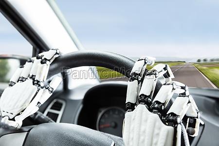 robotic hands on steering wheel