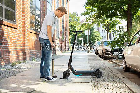 man pumping air into tire on