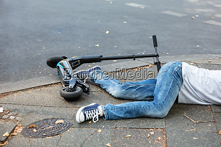 unconscious man lying on street after