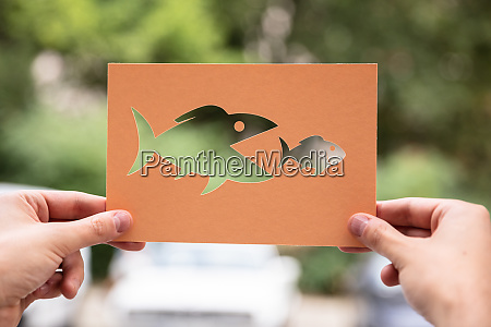 hands holding paper with cutout fish