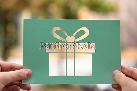 hands holding paper with cutout gift