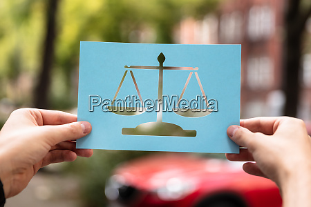hands holding paper with cutout law