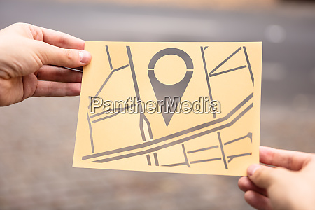 hands holding paper with cutout city