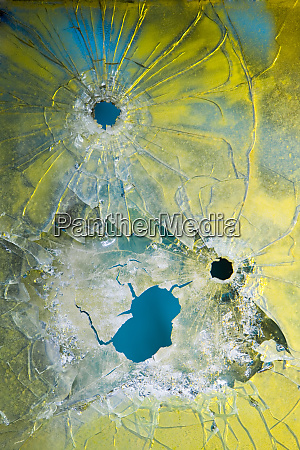bullet holes in fractured glass