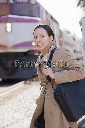 hispanic woman standing at a railway