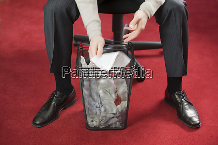 hispanic businessman searching in a wastepaper