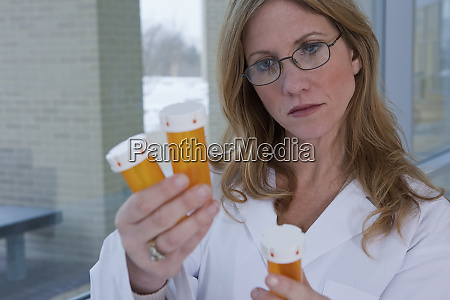female pharmacist checking pill bottles