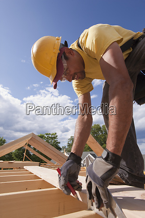carpenter marking spacing of rafters with