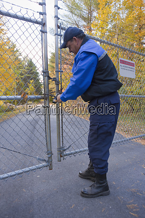 security guard locking a gate