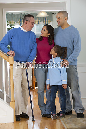 family standing together and smiling man