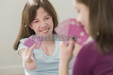 two teenage girls playing cards teenage