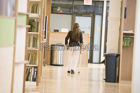 rear view of woman holding crutch