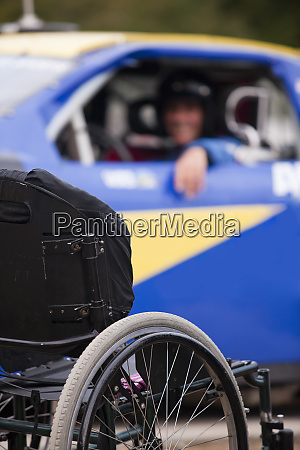 wheelchair in front of stock car