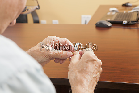 patient adjusting behind the ear hearing