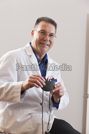 audiologist holding a hearing aid device