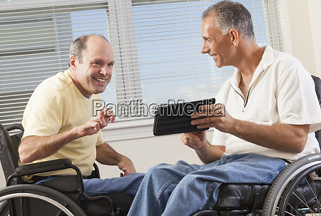 two disabled men sitting in wheelchairs