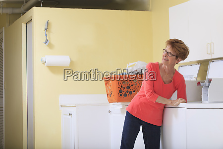 senior woman taking laundry out of