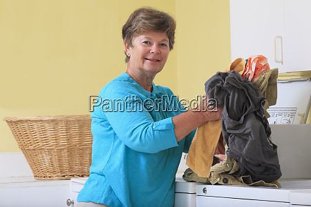 senior woman doing laundry in a