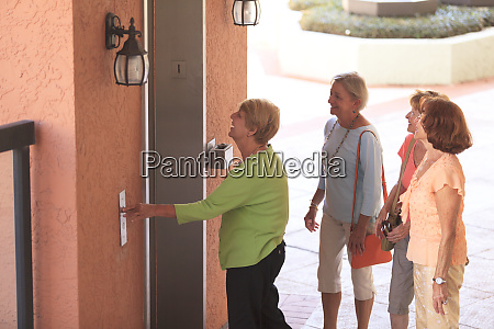 senior friends waiting to enter an