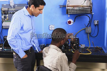 students examining condenser coil on refrigeration