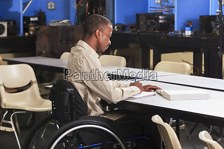 student in wheelchair taking notes while
