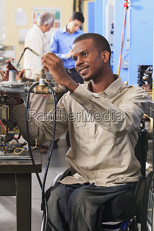student in wheelchair examining furnace ignitor