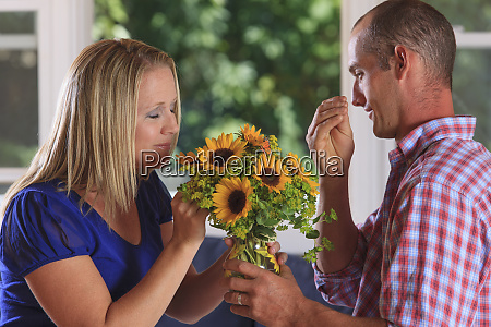 husband giving flowers to his wife