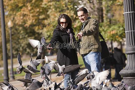 couple feeding pigeons