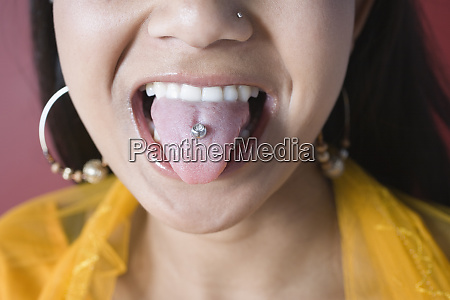 young woman showing her pierced tongue
