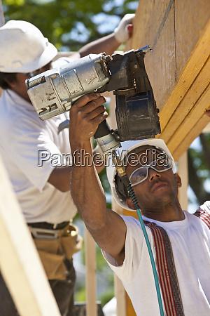 carpenters nailing beams