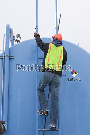 engineer climbing on a diesel tanker